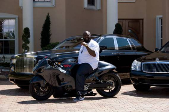 Rick Poss along with his motorbike and Rolls Royce Phantom parked behind him